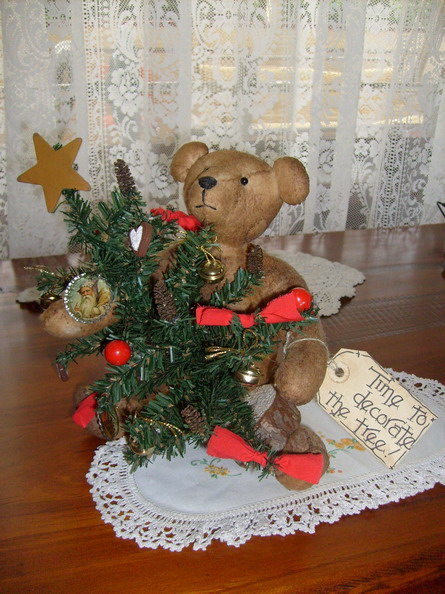 Handmade wool batting bear heavily stained and grubbied holding small